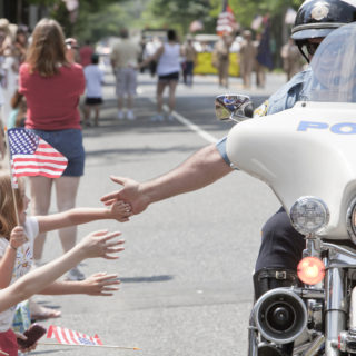 A Medford City policeman on a motorcycle gives patriotic children a high five showing community togetherness at Medford's anual Memorial Day parade.