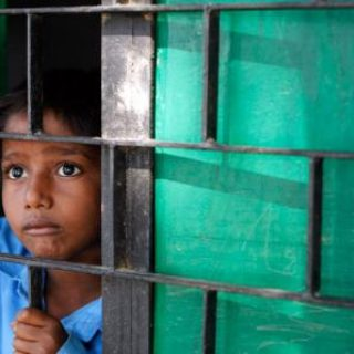 A child with a sad look, holding on to bars that he is behind