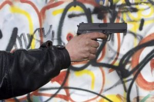Person with black jacket holding a black pistol against a graffiti coverred background
