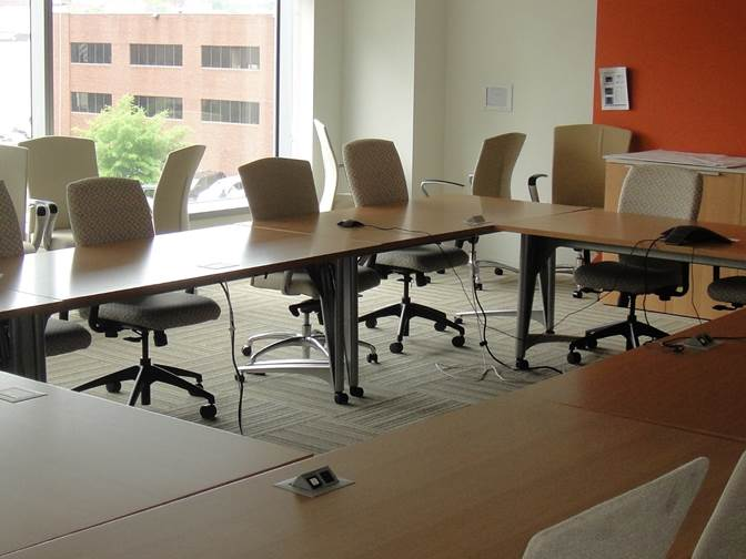 Quiet Office in Building sits Vacant of People as Table and Chairs Fill the Empty Space