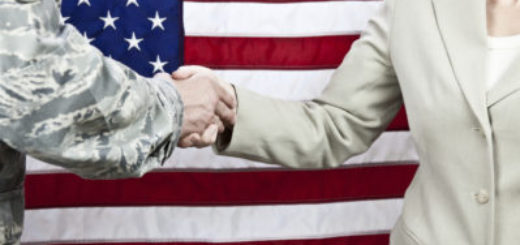 Member of military shaking hands of a civilian, with U.S. flag as background