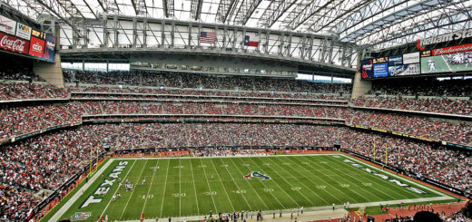 The interior of a large domed football stadium with fans in their seats and players on the field, which reads Texans and NFL in the inzone.