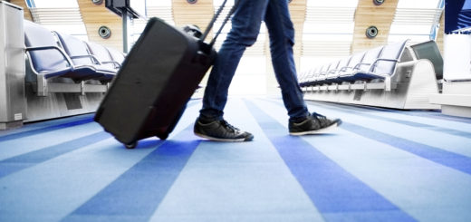 A man walks in airport while pulling luggage or a black suitcase while not rushing