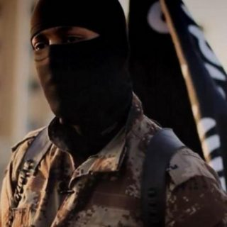 A masked jihadi poses in front of the ISIS flag