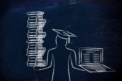 Grad holding books and laptop