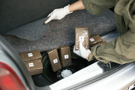 hand inspecting drug packages