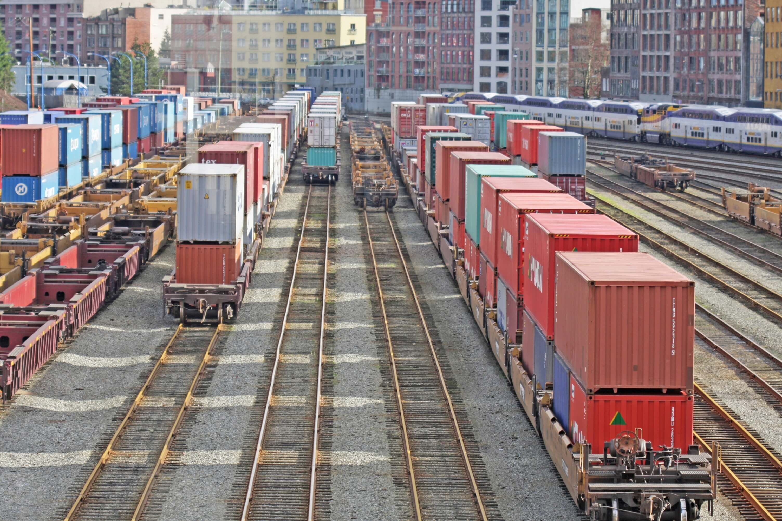Cargo containers near Burrard Inlet at Port Metro Vancouver. Background shows historic Gastown buildings in the north part of the city on a winter afternoon.