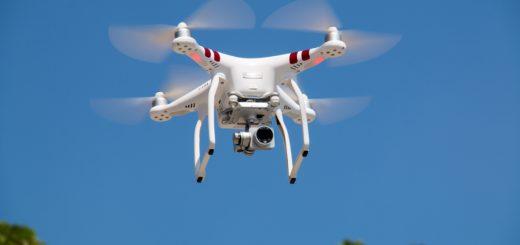white drone flying against blue sky
