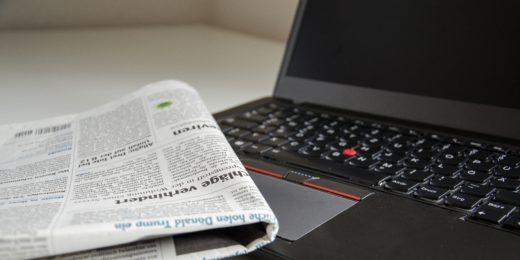 Newspaper placed on top of a laptop keyboard at a slight angle. The laptop screen is black.
