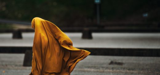 A woman in a flowing golden hijab walks on an empty street. She is facing away, and her face is hidden.