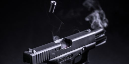 A black handgun before a black background. The gun has recently been fired, and both a shell and smoke can be seen