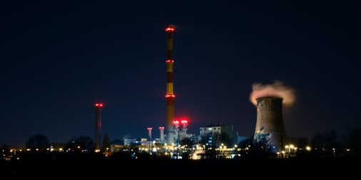 power plant in the dark with a cooling plant and a tower with red lights