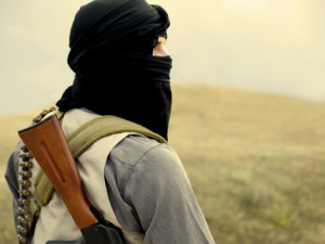Muslim militant with black fabric obscuring his head and face can be seen facing away. A rifle is draped over his shoulder.