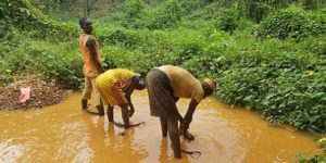 Illegal miners in Itagun, Nigeria separating mud, stones from the raw material, gold.