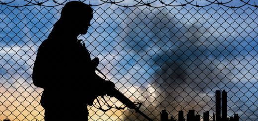 shadow of terrorist in front of fence with a city background