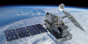 A large observatory satellite with solar wings extended hovers over the Earths atmosphere