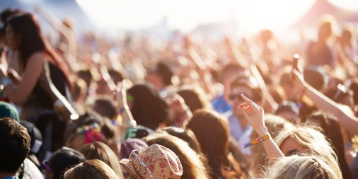 A young audience at a music festival cheers for an unseen musician or band
