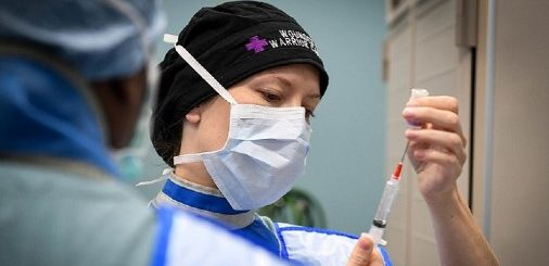 Female doctor in a black hat, wearing a surgical mask over her mouth and nose fills a syringe of medicine from a vial while nurse or doctor in the foreground looks on