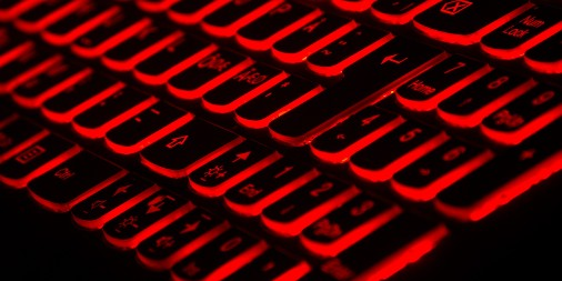 Close up of keyboard backlit by red lighting, focused on the keypad numbers 1-9