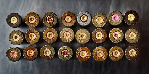 24 used bullet shells lined up in a rectangle of 3 by 8