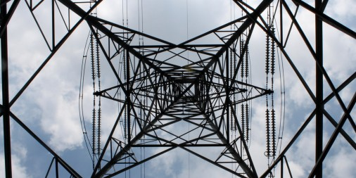 Underside of an electric tower with a cloudy sky in the background