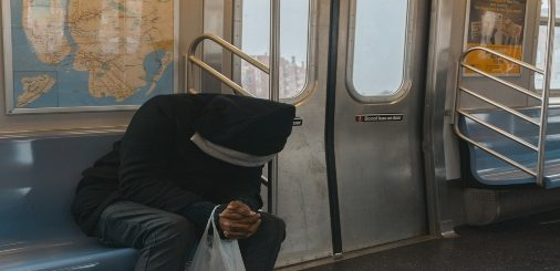 A man with his head down sitting on a train bench.