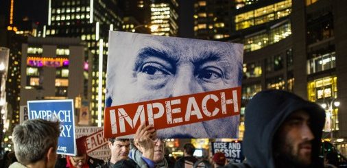 Man in a crowded city street at night holds sign with the top part of Trump's face with a red banner across his mouth that says impeach.