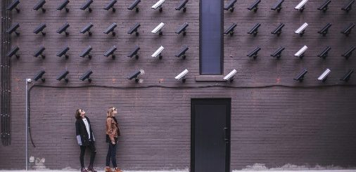 Two women stand next to a brown wall with dozens of mounted black and white surveillance cameras mounted to it