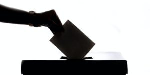 person dropping voting ballot