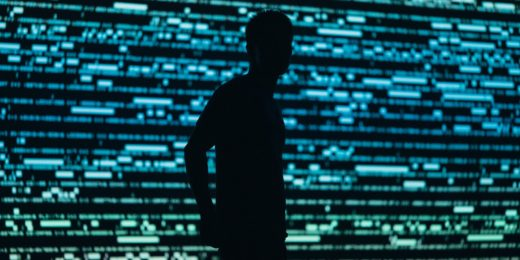 Profile silhouette of man standing in front of a background of green and blue horizontal lights