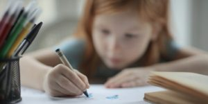 A girl holding coloring on a piece of paper near a book and a container of pens