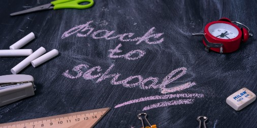 Back To School written in chalk on chalk board surrounded by school related items