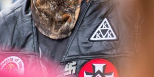 Close up of White Supremacist Group Patches on Black Leather Jacket and camouflaged neck covering