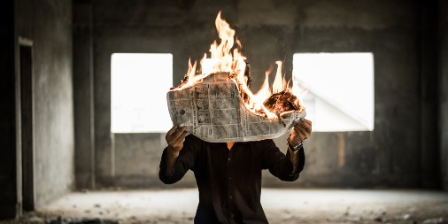 A man sitting in an empty room holds a flaming newspaper in front of his face