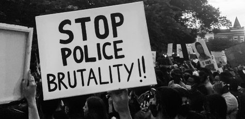 Black and white sign being held over a crowd that reads Stop Police Brutality