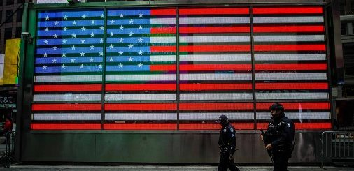 Two security guards walking in front of a large American flag