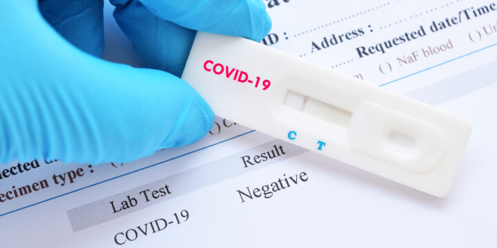 This image provides a close-up of a gloved hand holding a COVID-19 test, noting a negative result on both the test itself and on paperwork behind it