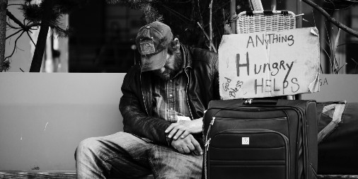 man with cardboard sign for food