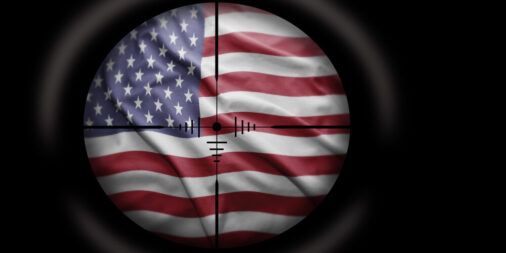 This image shows the United States flag within the scope of a sniper's gun, signifying hate and extremism in the U.S.