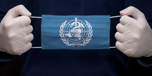 Health employee holding a medical face mask with WHO (World Health Organization) logo.