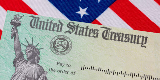 This image shows a close up of the United States Treasury check and American flag. Concept of stimulus payment, tax refund and federal government grants, loans, benefits and assistance.