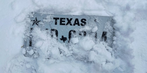 A Texas license plate partially covered in snow
