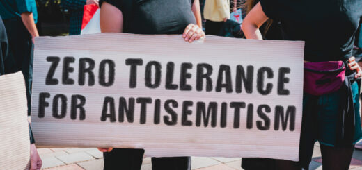 """A woman protests hatred against Jews by holding a sign that says """"zero tolerance for antisemitism."""""""