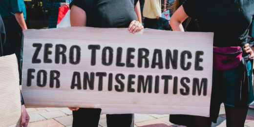 "A woman protests hatred against Jews by holding a sign that says ""zero tolerance for antisemitism."""