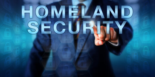 """An image of a faceless person touching the words """"Homeland Security"""" on a touch screen. Images of closed locks watermark the image, showing that national security is everyone's responsibility."""