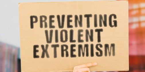 "Some holding up a cardboard message sign ""preventing violent extremism"""