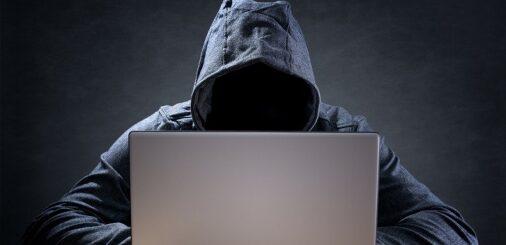 Dark figure behind computer / internet doing nefarious things.