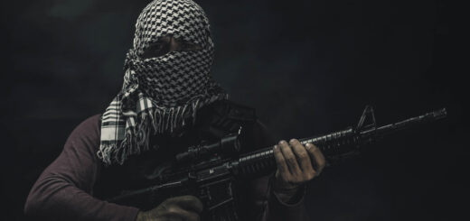 A militant threateningly holds up a rifle