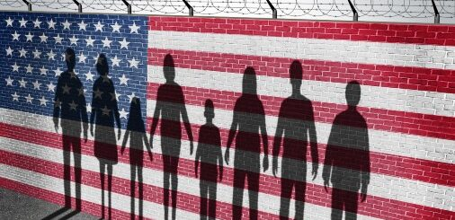 Silhouette of immigrants against a border wall with US flag