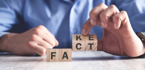 Two hands hold blocks. In one hand, the letters are F-A. The other hand holds two blocks that say K-E on one side and C-T on the other. Overall the blocks spell F-A-C-T or F-A-K-E.